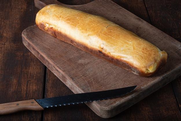 Pão caseiro recheado com frango desfiado em madeira rústica e faca