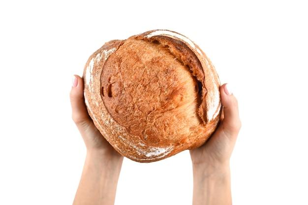 Pão caseiro redondo nas mãos, em um fundo isolado