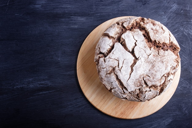 Pão caseiro sem fermento com grãos de centeio e trigo inteiros em fundo preto de madeira