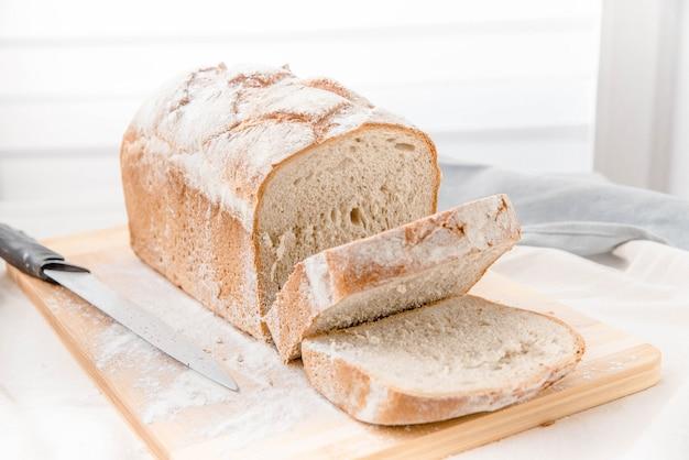 Pão caseiro sobre a faca de placa de corte
