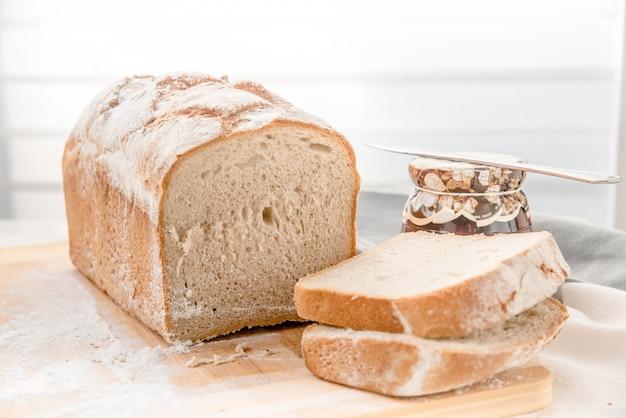 Pão caseiro sobre jam de placa de corte