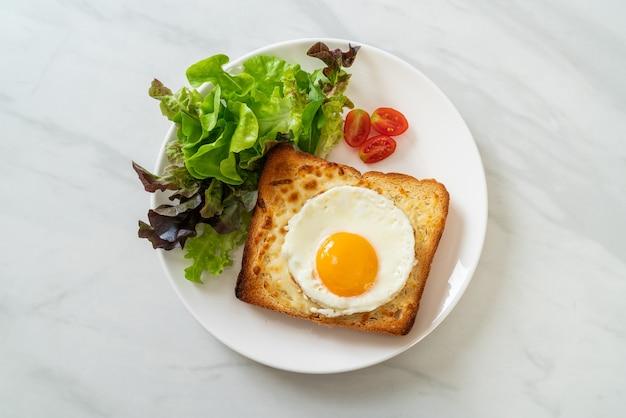 Pão caseiro torrado com queijo e ovo frito por cima com salada de legumes no café da manhã