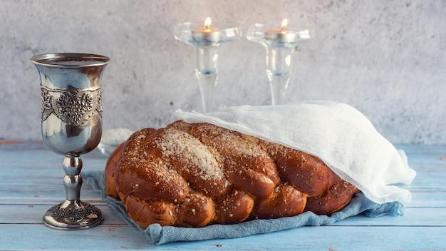 Pão chalá, vinho shabbat e velas na mesa de madeira