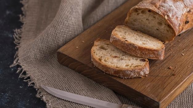 Pão ciabatta fatiado apetitoso na placa de madeira.