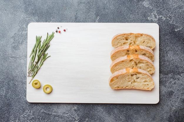 Pão ciabatta italiano com azeitonas e alecrim em um corte boardd