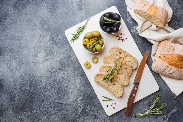 Pão ciabatta italiano com azeitonas e alecrim em uma placa de corte fundo escuro de concreto