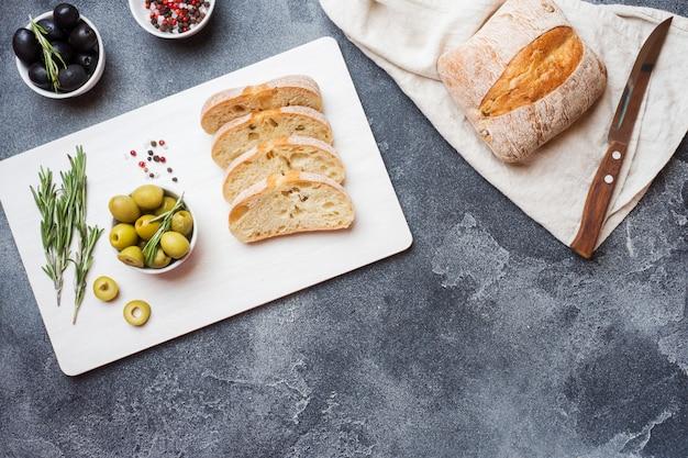 Pão ciabatta italiano com azeitonas e alecrim em uma placa de corte