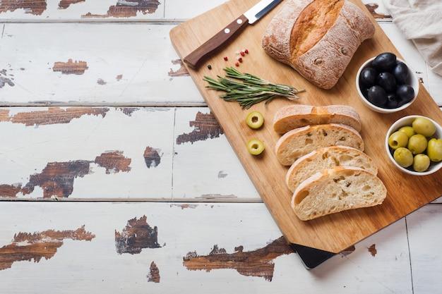 Pão ciabatta italiano com azeitonas e alecrim em uma placa de madeira