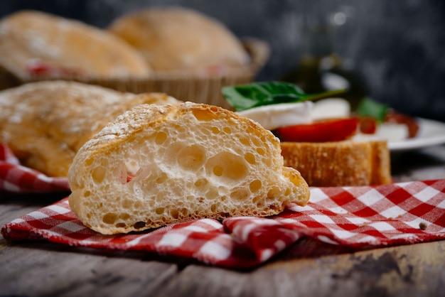 Pão ciabatta italiano tradicional com ervas como closeup no guardanapo xadrez