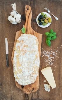 Pão ciabatta recém-assado com alho, azeitonas mediterrânicas, manjericão e queijo parmesão em servir a placa sobre madeira rústica