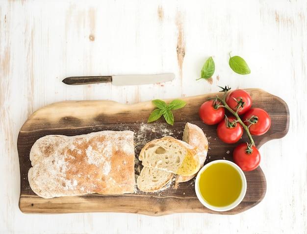 Pão ciabatta recém-assado com tomate cereja, azeite, manjericão e sal na placa de madeira de nogueira sobre branco, vista superior