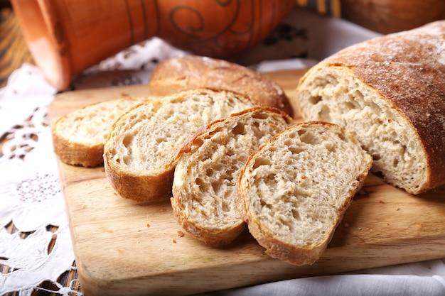Pão ciabatta recém-assados na tábua de madeira