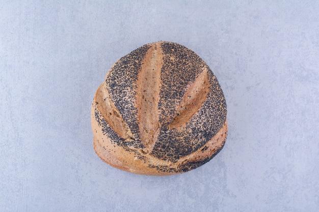Pão coberto de gergelim preto em superfície de mármore