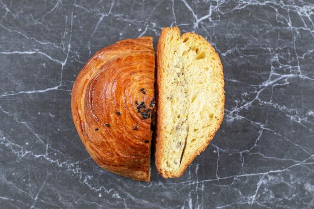 Pão colocado verticalmente e pão fatiado, sobre o mármore.