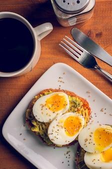 Pão com abacate, ovos cozidos e alguns grãos de café com gergelim e sal.