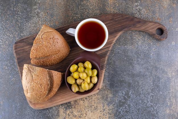 Pão com azeitonas verdes e uma xícara de chá