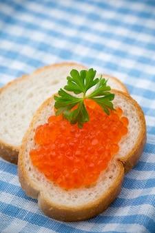 Pão com cream cheese fresco e caviar vermelho na mesa.