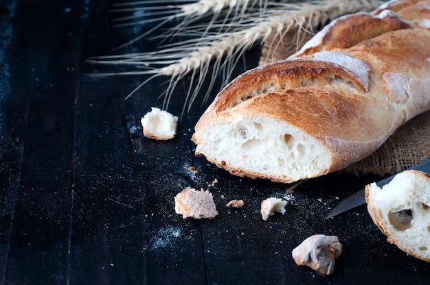 Pão com espigas de trigo na placa escura