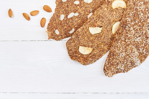 Pão com linhaça e amêndoas em uma madeira branca. pequeno-almoço vegan dietético útil com pão cru