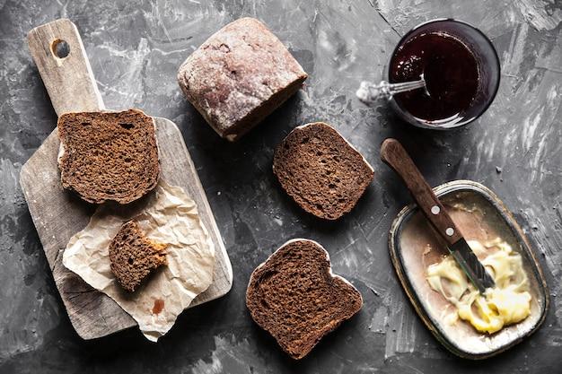 Pão com manteiga e geléia em estilo vintage em fundo escuro