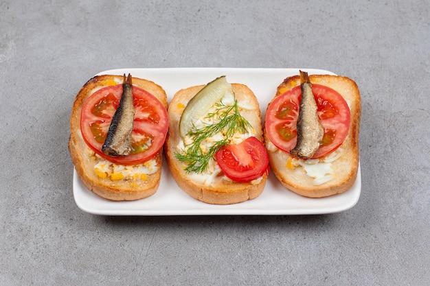 Pão com ovo mexido e peixe no prato branco