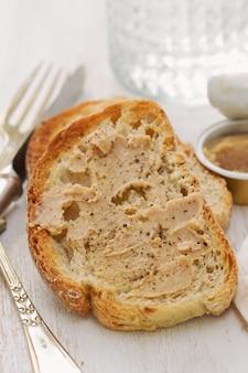 Pão com patê e copo de água no fundo de madeira branco