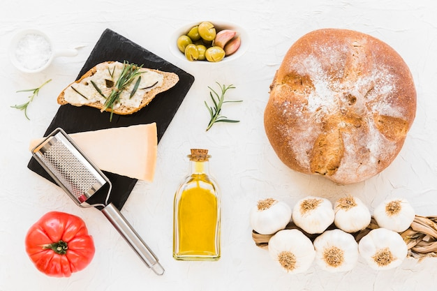 Pão com queijo, alecrim, óleo, tomate, azeitona com monte de bulbos de alho o pano de fundo branco