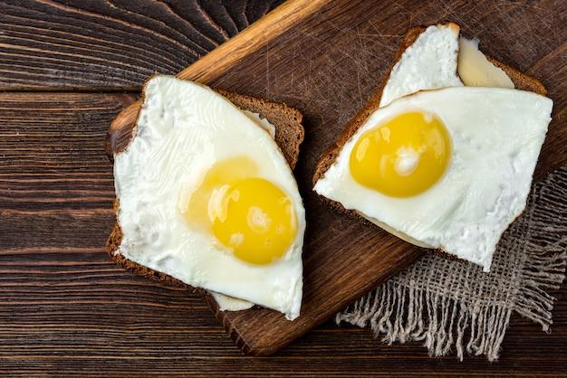 Pão com queijo e ovos no fundo escuro de madeira.