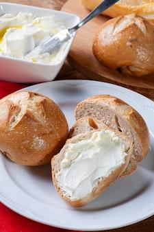 Pão com requeijão. prato branco e mesa de madeira.