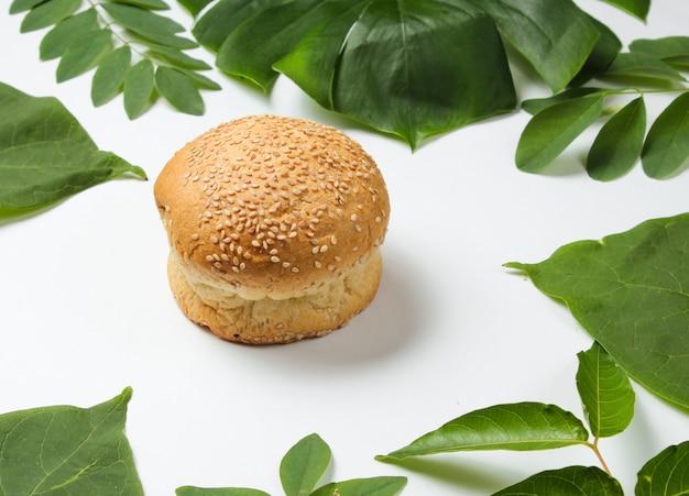 Pão com sementes de gergelim em um fundo branco com folhas tropicais verdes
