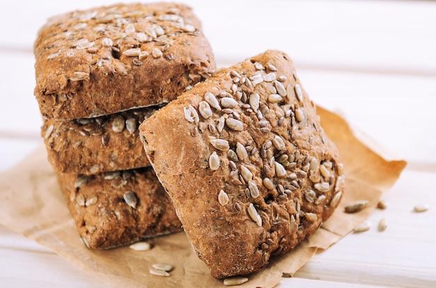 Pão com sementes de girassol em um fundo branco de madeira.