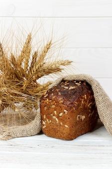 Pão com sementes e espigas de trigo na mesa de madeira