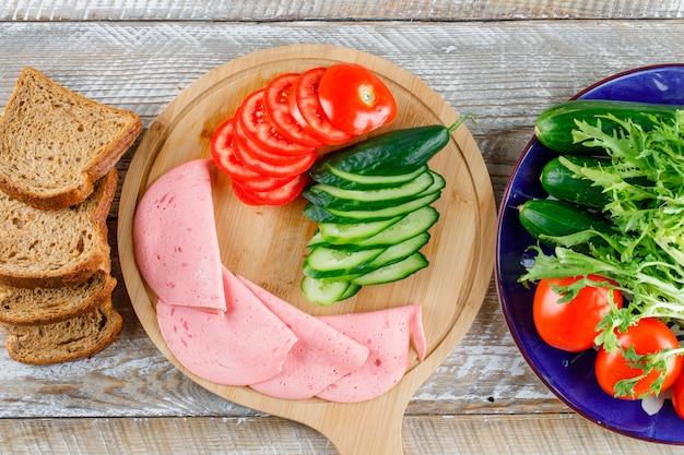 Pão com tomate, pepino, salsicha, verduras planas leigos na tábua de madeira e