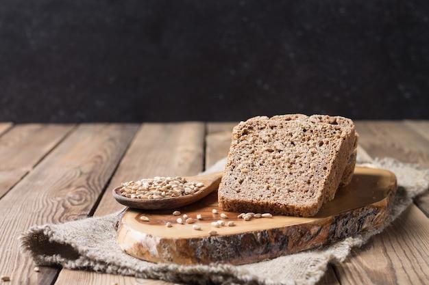 Pão cortado em pedaços, feito de farinha de espelta com fermento de farinha, repousa sobre a mesa da cozinha, sobre um fundo de madeira natural