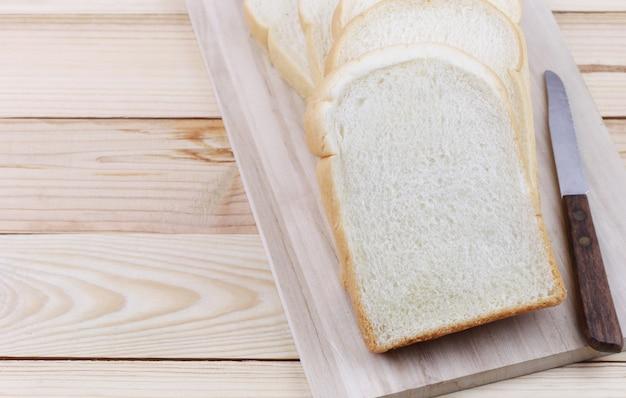Pão cortado empilhado em uma placa de desbastamento de madeira.