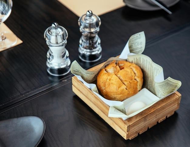 Pão cozido fresco servido com manteiga, sal e alho em moedores.