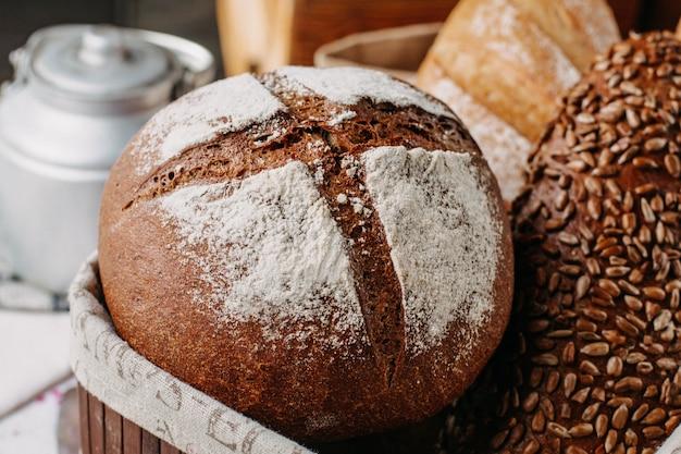 Pão cozido marrom e preto com farinha todo saboroso dentro da cesta