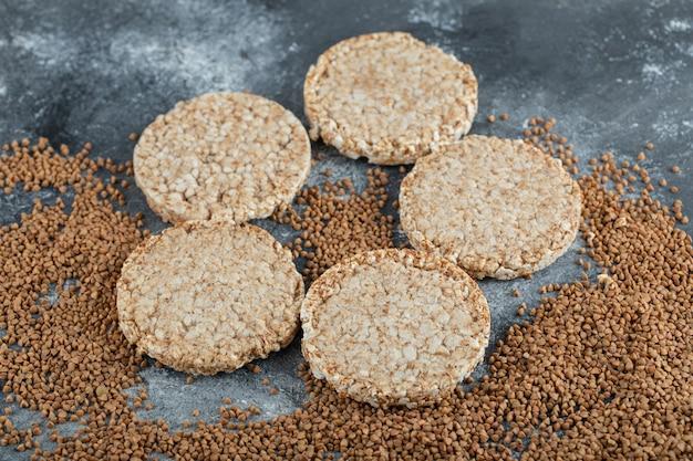 Pão crocante arejado e trigo sarraceno cru na superfície de mármore