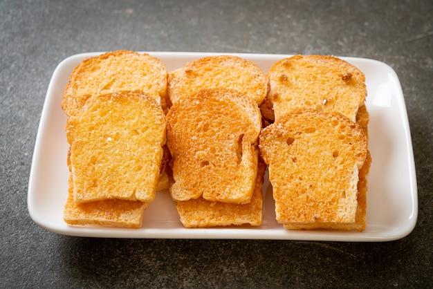 Pão crocante assado com manteiga e açúcar no prato