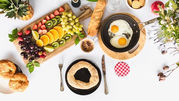 Pão crocante com pequeno-almoço saudável na mesa branca