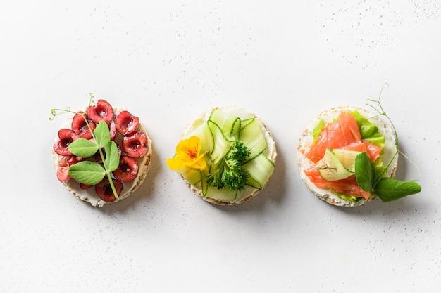 Pão crocante de arroz com diferentes coberturas de vegetais, frutas vermelhas e peixe vermelho, vista de cima saudável