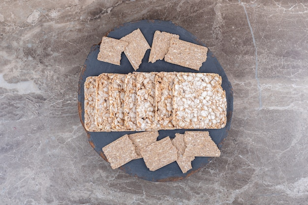 Pão crocante e bolinhos de arroz tufado em bandeja, na superfície de mármore