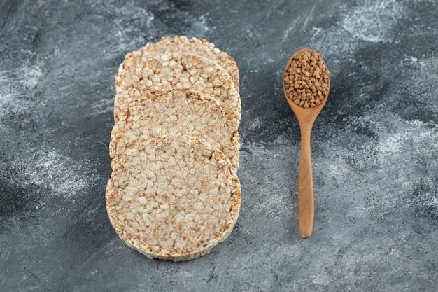 Pão crocante estufado e colher de pau de trigo sarraceno cru na superfície de mármore