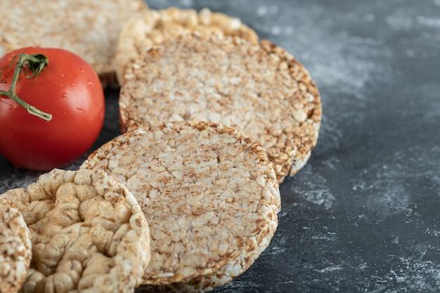 Pão crocante estufado e tomate fresco na superfície de mármore