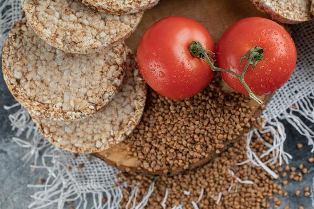 Pão crocante estufado, tomate e trigo sarraceno cru na superfície de mármore