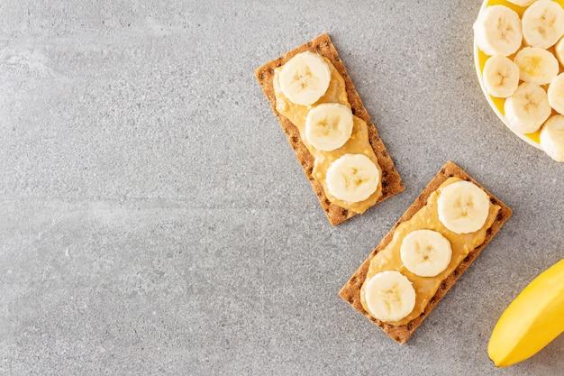 Pão crocante integral e manteiga de amendoim com pedaços de banana na mesa de pedra