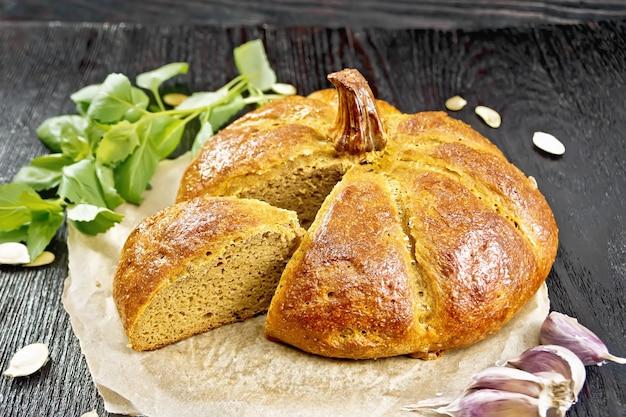 Pão de abóbora cortado em pergaminho, alho, manjericão e sementes em um fundo de tábua de madeira