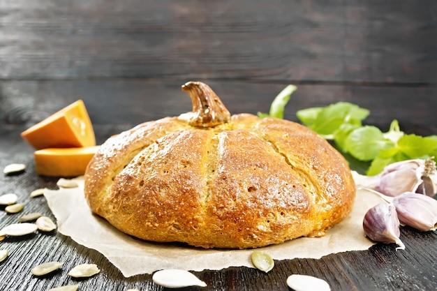 Pão de abóbora no papel, alho, manjericão, pedaços e sementes de um vegetal no fundo de uma placa de madeira escura