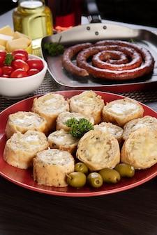 Pão de alho em um prato vermelho na mesa de churrasco com salsicha, queijo, alecrim, azeitonas e tomate cereja.