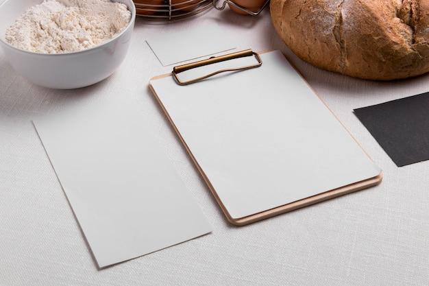 Pão de ângulo alto com prancheta em branco e farinha